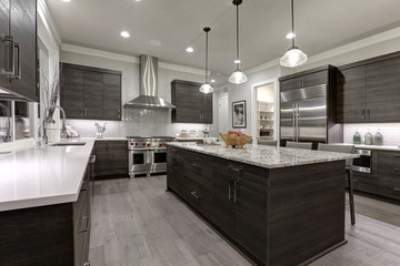 Modern gray kitchen features dark gray flat front cabinets paired with white quartz countertops and a glossy gray linear tile backsplash. Northwest, USA. Fotoväggar