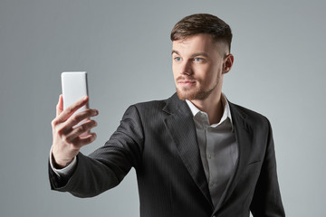 Businessman in a black suit makes the selfie on the smartphone