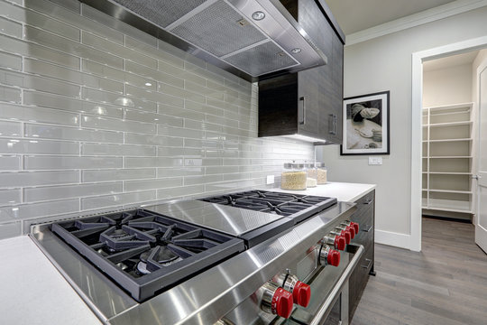 Modern gray kitchen features steel stove with a hood