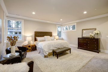 Beige and brown master bedroom boasts tufted queen bed