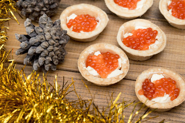 the Several tartlets with red caviar and butter tinsel fir coneson wooden brown table top view
