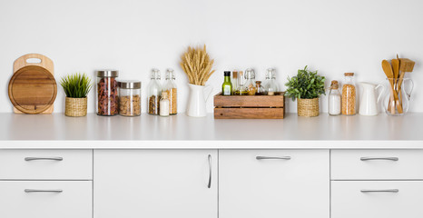 Kitchen bench shelf with various herbs, spices, utensils on white