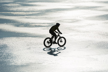 Man cycling on a frozen lake