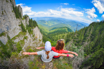 Two young women sitting on a cliff edge in the Ceahlau mountains in Romania