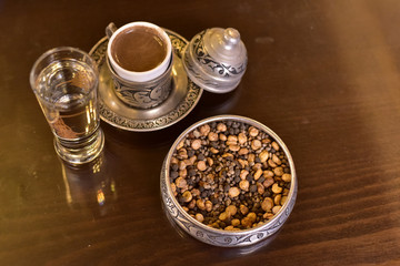 Traditional Turkish Coffee with some local dried nuts and water in Gaziantep, Turkey.