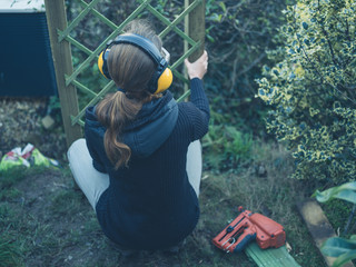Woman wearing ear muffs in garden
