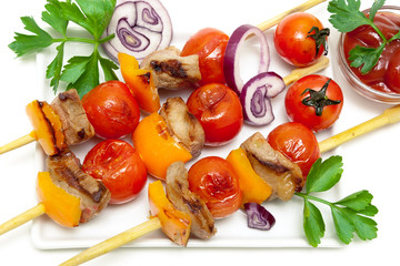 skewers of meat with vegetables and herbs  on a white background