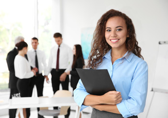 Business training concept. Beautiful woman with clipboard standing in office