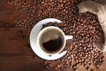 Cup of coffee with beans on table, top view