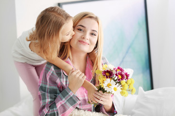 Little girl giving bouquet of beautiful flowers to her mother. Mother's day concept