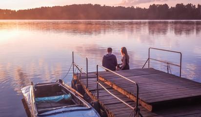 Romantic couple sitting pier golden sunset. Beautiful nature lake. man woman meet sunset. Beautiful couple outdoors near water