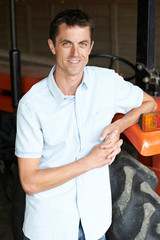 Portrait Of Farmer Standing In Barn With Tractor