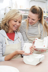 Teacher With Mature Woman Making Mug In Pottery Class