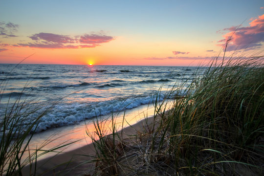 Tranquil Sunset Beach Background.  Beautiful sunset horizon over water with a sandy beach and dune grass in the foreground. Hoffmaster State Park. Muskegon, Michigan