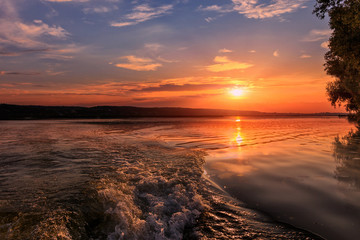 close-up texture of waves on the river at sunset, the trail from the boat. colorful clouds on the sky over the morning river. majestic misty sunrise. Beauty in the world. Ukraine.  Dniester