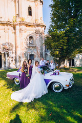 bride and groom with happy groomsmen and bridesmaids stay near old white retro car.