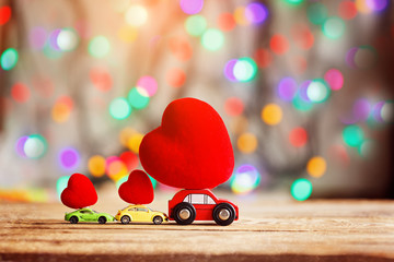 Miniature Car carrying a Red Heart on roof. Holiday concept love