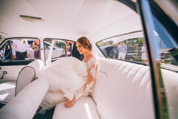 portrait of a pretty bride in retro car. Sunny day. Violet and white car color.