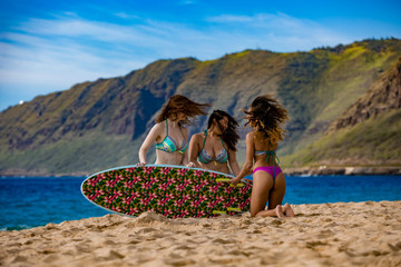 Three girls having fun at a beach with surfing board. Hawaiian vacation with sport activity. Blue water of Pacific ocean and green mountain at background