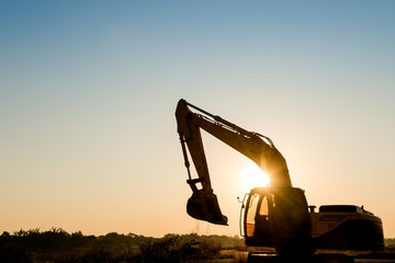 Track-type loader excavator machine on sunset background