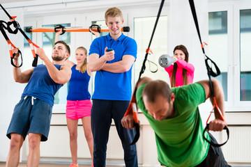 Sportler und Sportlerinnen beim Ringeturnen im Fitness-Club mit Physiotherapeut