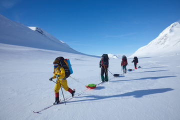 Ski touring group with backpacks and sleds (pulkas)