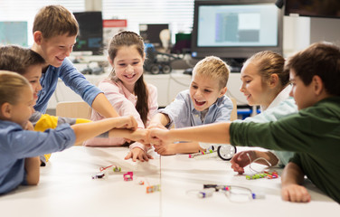 happy children making fist bump at robotics school