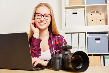 Photographer with laptop and camera in her office