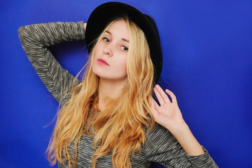Blonde girl hipster in a grey sweatshirt and a black round hat looking directly into the camera.
