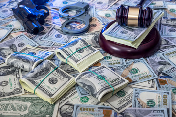 handcuffs and judge gavel, gun and money on brown wooden table.