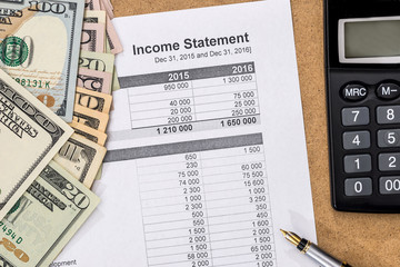 Save money concept - doc income statement with pen, calculator and money.