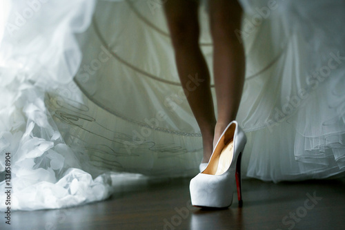 """""""Bride puts on her shoes raising wedding dress up"""" Stock ..."""