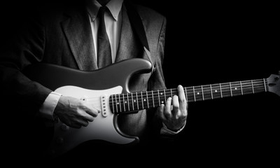male musician in suit playing electric guitar, black and white. isolated on black