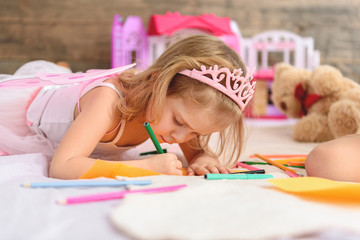 Child drawing pictures in bedroom