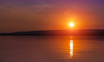 sunset over the lake. sun reflected in water. unusual picturesque scene. beauty in the world