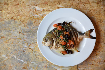 Whole fish garnished with vegetables, overhead view