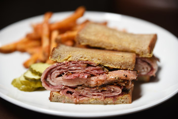 Pastrami sandwich, french fries, gherkin