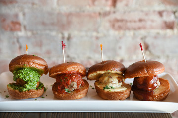 Meatball burgers in a row on serving dish