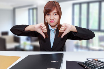 Unhappy business woman with thumb down in office - calculator