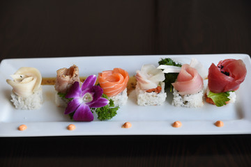 Fresh sushi on serving dish garnished with flower