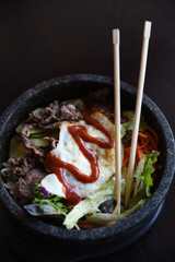 Bibimbap bowl with chopsticks, overhead view