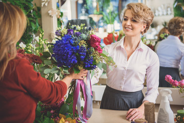 Happy woman serving customer in flower shop
