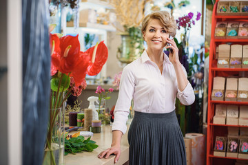 Happy woman using smartphone at flower shop