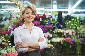 Cheerful woman working in flower shop