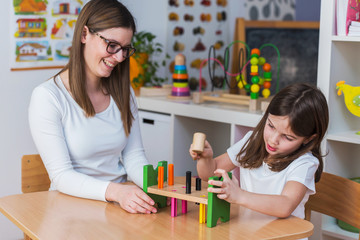 Woman and child are playing together with didactic toys