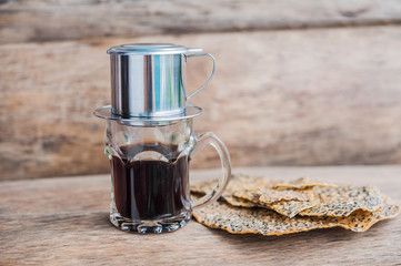 'Phin' traditional Vietnamese coffee maker, add ground coffee then pour hot water and wait until the coffee dripping into the glass. The Vietnamese Sesame Rice Cracker is called Banh Da