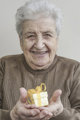 Senior woman holding a small gift
