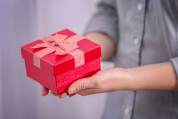 Woman holding beautiful gift box, closeup