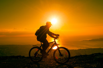 Silhouette of cyclist riding on a bike in mountain at sunset