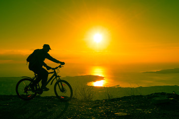 Silhouette of cyclist riding on a bike in mountain at sunset. To